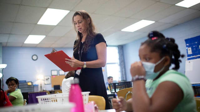 Jennifer Potts takes attendance for her fourth-grade class as her student Aleiha Hill listens during the start of a new school year at Joseph Brown Elementary School in Columbia, Tenn., on Monday, Aug. 10, 2020.