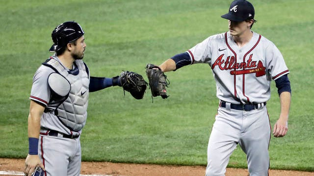 Atlanta Braves catcher Travis d'Arnaud, left, bumps gloves with starting pitcher Max Fried after Fried struck out the side during the fourth inning of the team's baseball game against the Miami Marlins Saturday in Miami.