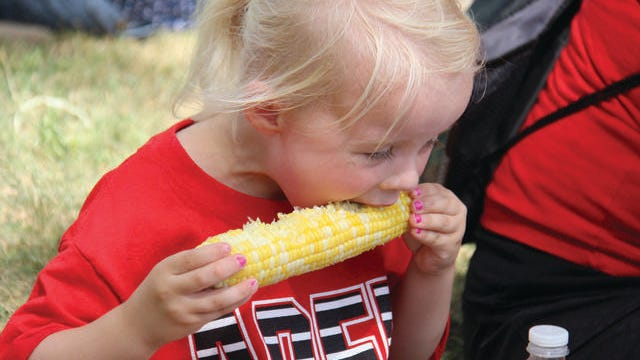 Cora Johnston, 4, of Adel eats a piece of sweet corn during the 2019 Sweet Corn Festival. COVID-19 concerns prompted the cancellation of the 2020 festival. PHOTO BY ALLISON ULLMANN/DALLAS COUNTY NEWS