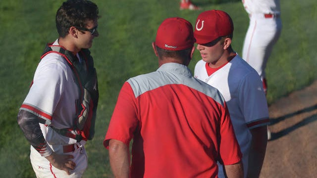 DCG head baseball coach Byron Peyton talking with catcher Cole Wessling and pitcher Logan Smith following the top half of the first Monday, July 20 against Carroll in the substate semi-final. PHOTO BY ANDREW BROWN/DALLAS COUNTY NEWS