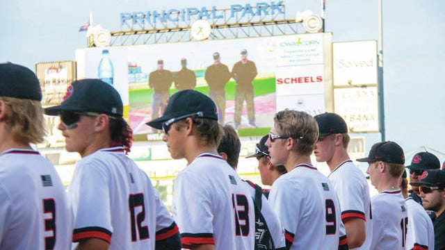 The Gilbert baseball team lines up along the first-base line prior to the Tigers' game against ADM in the quarterfinals of the Class 3A state baseball tournament on Tuesday night at Principal Park in Des Moines. Photo by Sean Cordy