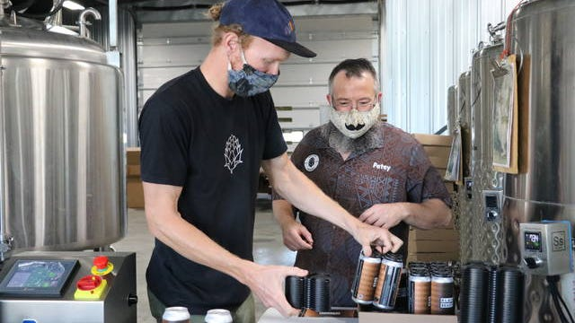 Elliot Thompson, owner of Alluvial Brewing Company, and Jason Peterson, head brewer, package the Black is Beautiful stout into four-packs, which are available for sale through the brewery's website. Photo by Kylee Mullen/Ames Tribune