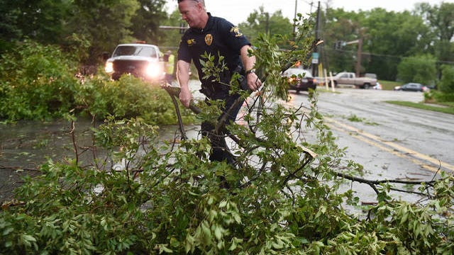Officer Bud Samms of the Ames Police Department moves tree branches from the road after heavy storm at Grand Avenue on Monday in Ames. Photo by Nirmalendu Majumdar/Ames Tribune