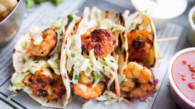 Rock Star Shrimp tacos, with Grilled jumbo shrimp in corn tortilla tacos with cabbage garnish on an old fashioned newspaper wrapper.