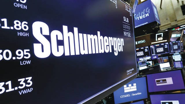 The logo for Schlumberger appears above a trading post on the floor of the New York Stock Exchange on Oct. 8, 2019. Schlumberger is cutting more than 21,000 jobs and paying $1.02 billion in severance as declining oil prices amid the coronavirus pandemic push it to slash costs. Richard Drew/AP file