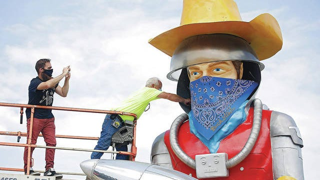 Artist Adam Carnes, left and Gary Coulson place a mask on Buck Atom, the mascot of Buck Atom's Cosmic Curios Route 66, Friday, July 17, 2020, in Tulsa. The city now has a mask mandate to protect against the spread of COVID-19. Mike Simons/Tulsa World via AP