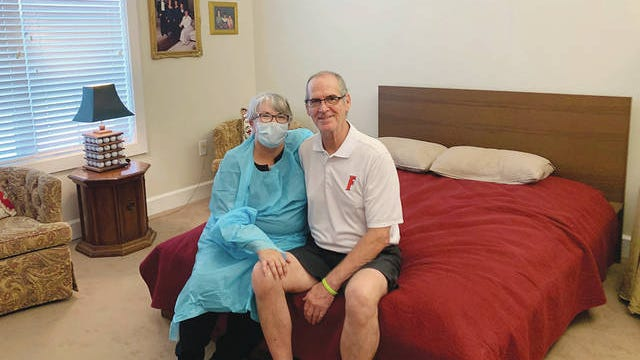 Mary Daniels and her husband, Steve, sit together in his room Monday, July 13, 2020, at the Rosecastle at Deerwood assisted facility in Jacksonville, Fla, Mary went 114 days without seeing her husband who has early onset of Alzheimers, after the coronavirus forced the facility to ban all visitors. She took a job as a part-time dishwasher at the facility so that she is able to see her husband. Rosecastle at Deerwood via AP