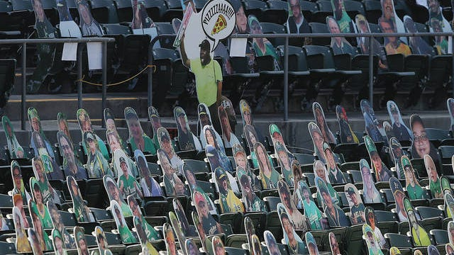Cardboard cutouts of a vendor, fans and former Oakland Athletics players are placed in seats at Oakland Coliseum before a baseball game between the Athletics and the Los Angeles Angels in Oakland, Calif., Friday, July 24, 2020. Jeff Chiu/AP