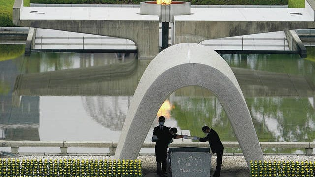 Kazumi Matsui, right, mayor of Hiroshima, and the family of the deceased bow before they place the victims list of the Atomic Bomb at Hiroshima Memorial Cenotaph during the ceremony to mark the 75th anniversary of the bombing at the Hiroshima Peace Memorial Park Thursday, Aug. 6, 2020, in Hiroshima, western Japan. Eugene Hoshiko/AP