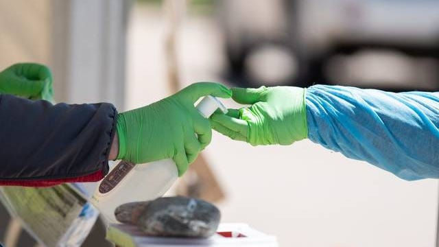 Nurses put hand sanitizer on their gloves before taking another nasal swab for COVID-19 testing at the Chickasaw Nation Purcell Health Clinic on April 28. Whitney Bryen/Oklahoma Watch file