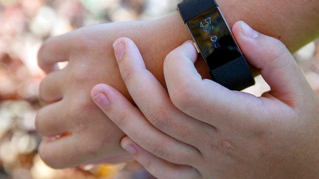 """Grace Brown, 14, adjusts her fitness tracker at the park where she does her jogging workouts for her """"online PE"""" class, in Alexandria, Va., on Nov. 1, 2019. Brown chose to take """"online PE,"""" utilizing a fitness tracker, so that she could take a piano lab as an extra elective."""