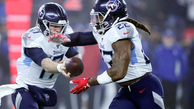 Tennessee Titans quarterback Ryan Tannehill, left, hands off to running back Derrick Henry in the first half of an NFL wild-card playoff football game against the New England Patriots on Jan. 4 in Foxborough, Mass.