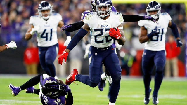 Tennessee Titans running back Derrick Henry (22) runs past Baltimore Ravens strong safety Chuck Clark (36) during the second half of an NFL divisional playoff football game on Saturday in Baltimore.