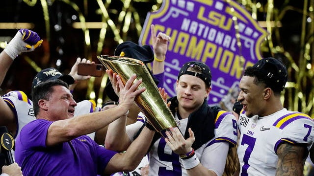 LSU head coach Ed Orgeron, left, and quarterback Joe Burrow, center, hold the trophy beside safety Grant Delpit after a NCAA College Football Playoff national championship game against Clemson, Monday, in New Orleans. LSU won 42-25.