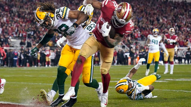 San Francisco 49ers running back Raheem Mostert, center right, scores a touchdown next to Green Bay Packers cornerback Tramon Williams during the second half of the NFL NFC Championship football game Sunday in Santa Clara, Calif.