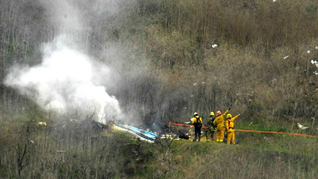 Firefighters work the scene of a helicopter crash where former NBA star Kobe Bryant died, Sunday in Calabasas, Calif.