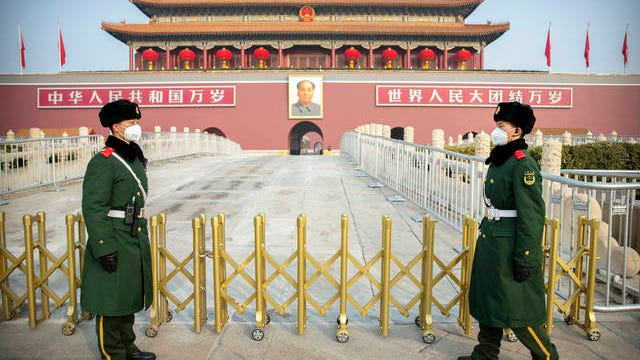 Paramilitary police wear face masks as they stand guard at Tiananmen Gate adjacent to Tiananmen Square in Beijing on Monday. China on Monday expanded sweeping efforts to contain a viral disease by postponing the end of this week's Lunar New Year holiday to keep the public at home and avoid spreading infection.
