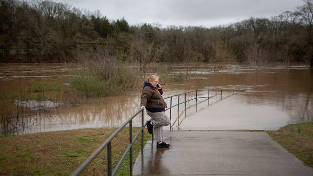 Columbia resident Tammy Dick takes a phone call near a flooded walkway at the banks of the Duck River at Riverwalk Park in Columbia on Thursday, Feb., 6, 2020.