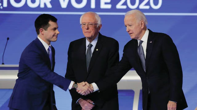 From left, Democratic presidential candidates former South Bend Mayor Pete Buttigieg, shakes hands with former Vice President Joe Biden as Sen. Bernie Sanders, I-Vt., watches Friday before the start of a Democratic presidential primary debate hosted by ABC News, Apple News and WMUR-TV at Saint Anselm College in Manchester, N.H.