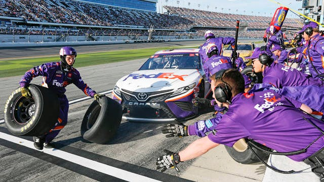 Denny Hamlin's crew changes tires and refuels during a pit stop during the NASCAR Daytona 500 auto race at Daytona International Speedway on Monday. in Daytona Beach, Fla. Sunday's race was postponed sue to rain.