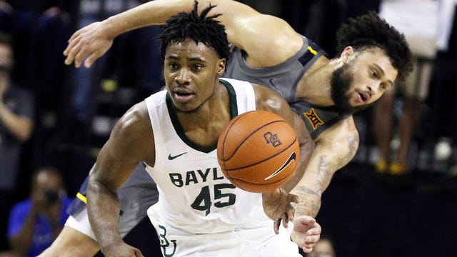 Baylor guard Davion Mitchell, left, breaks away from West Virginia guard Jermaine Haley for a fast break in the second half of an NCAA college basketball game on Feb. 15 in Waco, Texas.