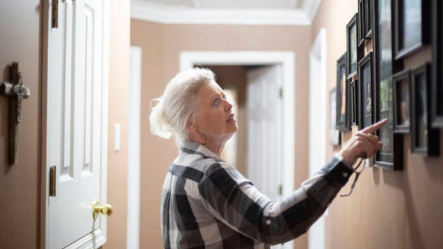 """Catherine Pence looks at photographs of her son Paul """"J.R."""" Hayward who was murdered in 2015 inside the home of her daughter in Columbia on Tuesday, Feb. 18, 2020."""