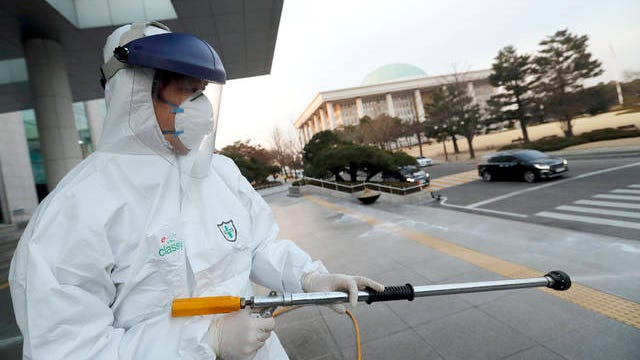 """A worker wearing a protective suit sprays disinfectant as a precaution against the coronavirus at the National Assembly in Seoul, South Korea, Monday. South Korea reported another large jump in new virus cases Monday a day after the president called for """"unprecedented, powerful"""" steps to combat the outbreak that is increasingly confounding attempts to stop the spread."""