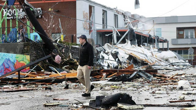 A man walks past storm debris following a deadly tornado Tuesday, in Nashville. Tornadoes ripped across Tennessee early Tuesday, shredding buildings and killing multiple people.