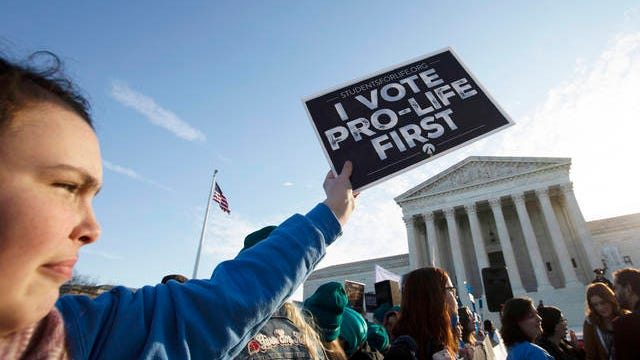 Anti-abortion demonstrators rally outside of the U.S. Supreme Court in Washington on Wednesday. The Supreme Court is taking up the first major abortion case of the Trump era Wednesday, an election-year look at a Louisiana dispute that could reveal how willing the more conservative court is to roll back abortion rights.