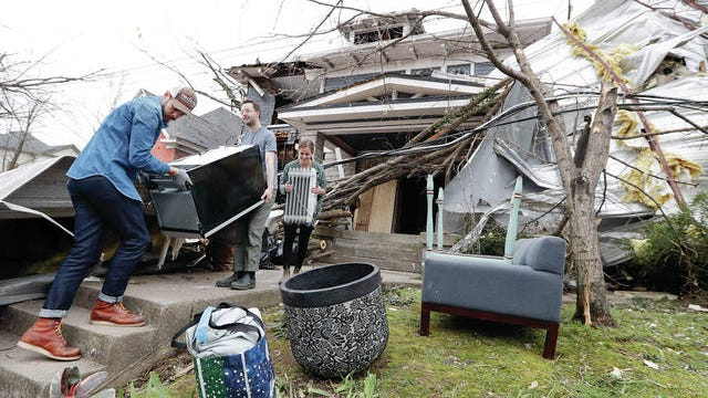 Benji Peck, left, and Austin Grove remove a refrigerator from a damaged home Wednesday, in Nashville. Residents and businesses face a huge cleanup effort after tornadoes hit the state Tuesday.