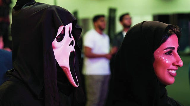 Two Emiratis watch a dance-off at the Middle East Film & Comic Con in Dubai, United Arab Emirates, Thursday. The Middle East Film & Comic Con began Thursday night in Dubai, a city of skyscrapers and nightclubs suddenly subdued by the outbreak of the new coronavirus across the region.