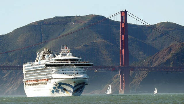 In this photo, the Grand Princess cruise ship passes the Golden Gate Bridge as it arrives from Hawaii in San Francisco. California's first coronavirus fatality is an elderly patient who apparently contracted the illness on a cruise, authorities said Wednesday, and a medical screener at Los Angeles International Airport is one of six new confirmed cases. The cruise ship is at sea but is expected to skip its next port and return to San Francisco by Thursday, according to a statement from Dr. Grant Tarling, the chief medical officer for the Carnival Corp., which operates the Grand Princess. Any current passengers who were also on the February trip will be screened.