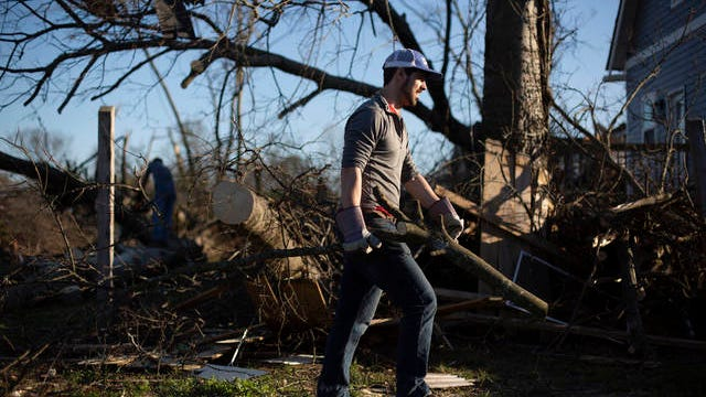 Jay Renfro, an ecology teacher from Antioch, carries a piece of a downed tree from the backyard of a home in the Ossage/North Fisk neighborhood of Nashville during a tornado cleanup effort on Thursday, March 5, 2020.
