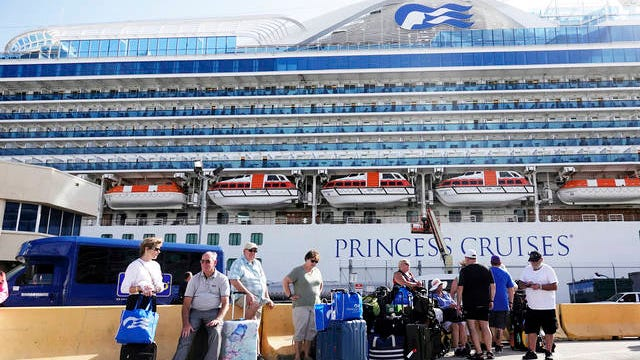 In this Feb. 13 file photo, passengers from the Caribbean Princess wait for ground transportation at Port Everglades in Fort Lauderdale, Fla. Princess Cruises confirmed on Monday that the Caribbean Princess was ordered by the CDC to keep its passengers and crew on board while crew members get tested for COVID-19.
