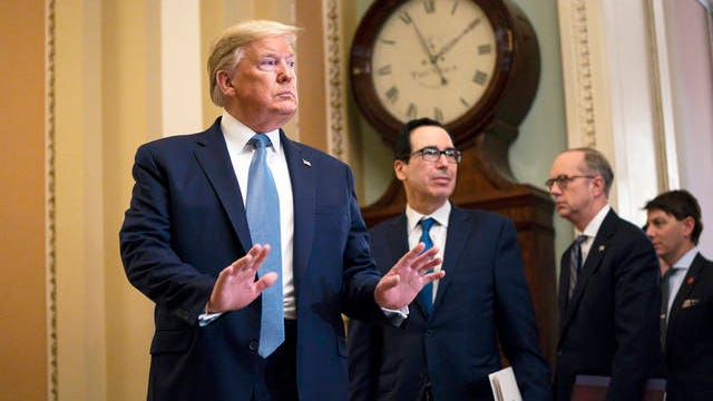 Treasury Secretary Steven Mnuchin listens and President Donald Trump arrives to speak with reporters after meeting with Republican lawmakers on Capitol Hill Tuesday in Washington.