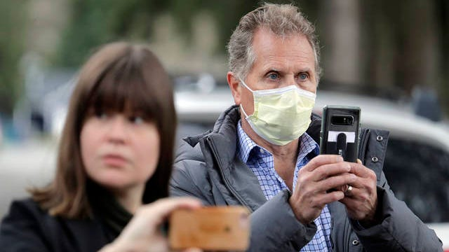 Scott Sedlacek, right, who says he has tested positive for the COVID-19 coronavirus, wears a mask and uses his phone to film a news conference held Wednesday at the Life Care Center in Kirkland, Wash., near Seattle. Sedlacek's father Chuck Sedlacek, 86, also is positive for the virus and is a patient in the nursing home, which is at the center of the outbreak of the COVID-19 coronavirus in Washington state.