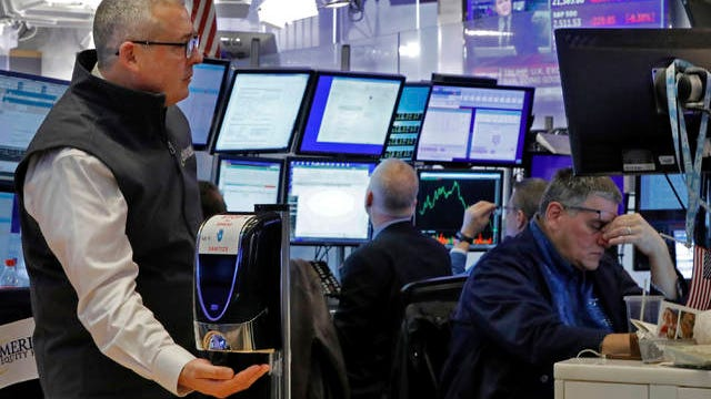 A trader uses a hand sanitizer dispenser on the floor of the New York Stock Exchange, Thursday. The deepening coronavirus crisis sent stocks into another alarming slide on Wall Street, triggering a brief, automatic shutdown in trading for the second time this week.