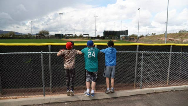 Young fans look over the fences at Tempe Diablo Stadium in Arizona.