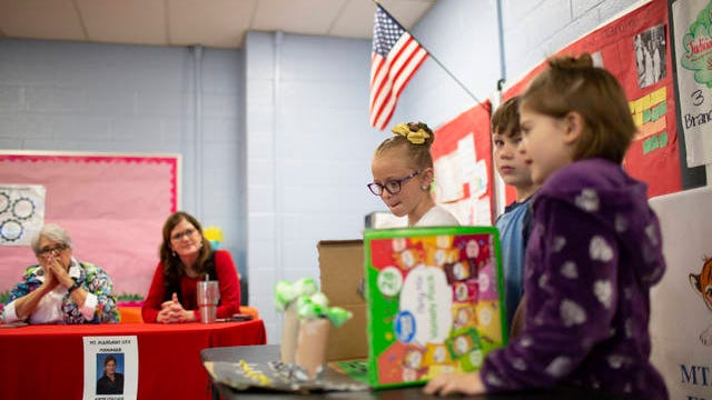 Mt. Pleasant Elementary students Katie Bozeman, 8, Lily An Howell, 8, and Levi William Horn, 7, present their proposal for a new sidewalk in Mt. Pleasant before Commissioner Delores Blankenship and City Manager Kate Collier on Friday, March 13, 2020.