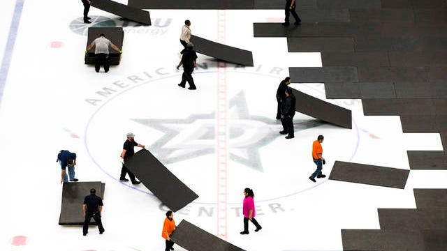 Crews cover the ice at American Airlines Center in Dallas, home of the Dallas Stars hockey team, after the NHL season was put on hold due to coronavirus on March 12.