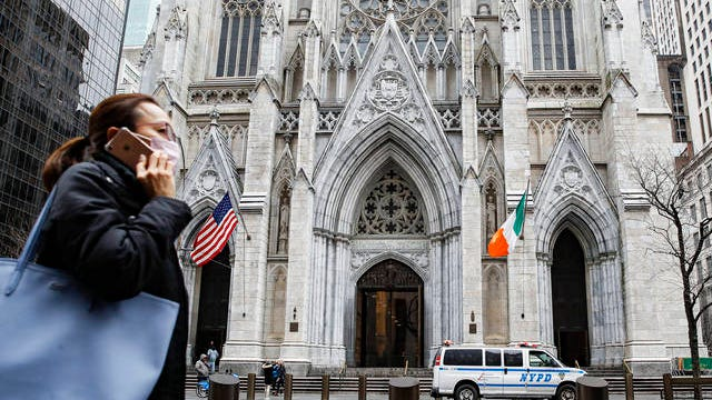 A pedestrian wearing a protective mask walks by St. Patrick's Cathedral after the annual St. Patrick's Day parade was cancelled due to coronavirus concerns on Tuesday in New York.