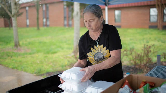 Deena McKervey distributes meals to children at Spring Hill High School on Wednesday, March 18, 2020.