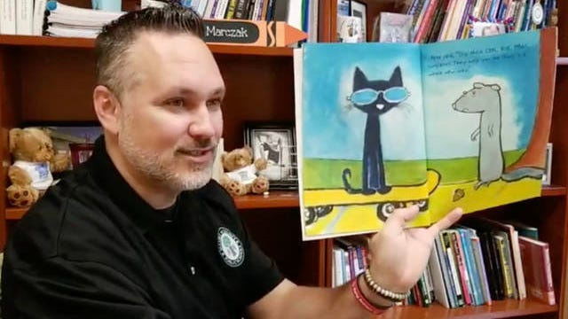 """Maury County Public Schools Superintendent Chris Marczak reads a """"Pete the Cat"""" book to students on a live internet braodcast on Monday."""