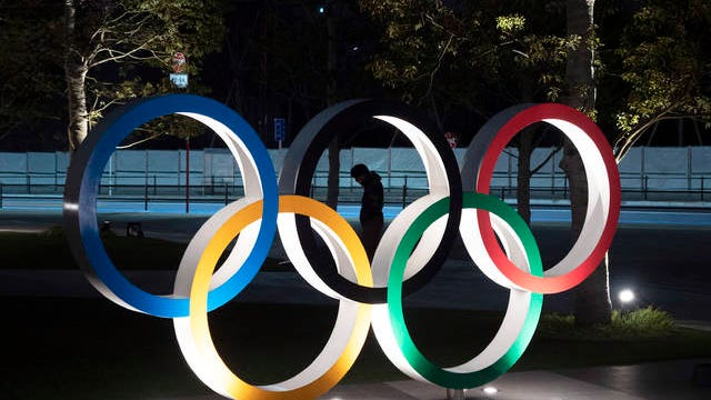 "A man is seen through the Olympic rings in front of the New National Stadium in Tokyo on Tuesday. IOC President Thomas Bach has agreed ""100%"" to a proposal of postponing the Tokyo Olympics for about one year until 2021 because of the coronavirus outbreak, Japanese Prime Minister Shinzo Abe said Tuesday."