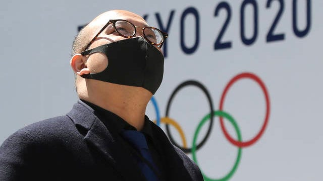 A man walks in front of a Tokyo Olympics logo at the Tokyo metropolitan government headquarters building Wednesday, following the Tuesday delay of the torch relay. The 2020 Games have been pushed back to 2021.