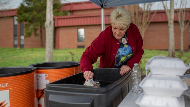 Sandy Green, the assistant manager of food services at Spring Hill High School, distributes meals to children at the high school on Wednesday.