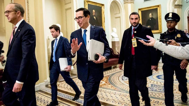 Treasury Secretary Steven Mnuchin, third from left, and White House Legislative Affairs Director Eric Ueland, left, walk to a meeting with Senate Minority Leader Sen. Chuck Schumer of N.Y. in his office on Capitol Hill on March 23 in Washington. The Senate is working to pass a coronavirus relief bill.