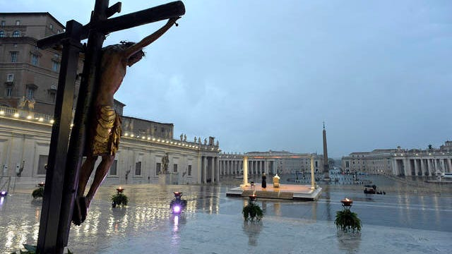 A crucifix, believed to be miraculous, that in 1552 was carried in a procession around Rome to stop the great plague, left, frames Pope Francis, white figure sitting beneath the canopy, as he delivers an Urbi and Orbi prayer (Latin for To the City and To the World) from an empty St. Peter's Square, at the Vatican, Friday.