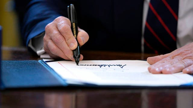 President Donald Trump signs the coronavirus stimulus relief package in the Oval Office at the White House, Friday, in Washington.