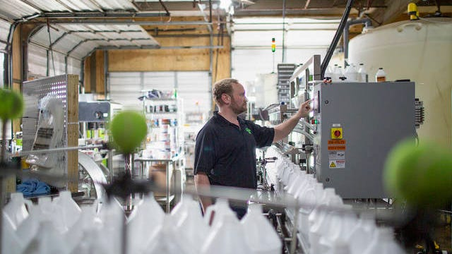 Adam Pouge, the chief executive officer of Froggys Fog, demonstrates how the Columbia company will bottle its hand sanitizer on Friday, March 27, 2020. In a matter of days, the company shifted operations from manufacturing the fluid used in creating artificial fog to hand sanitizer amid the national economic shutdown caused by the spread of the novel coronavirus. The new product is called Froggys Simply Sanitizer.